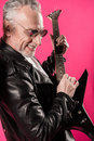 Stylish senior man in sunglasses playing rock and roll music with electric guitar Royalty Free Stock Photo