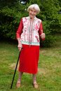 Stylish senior woman giving a thumbs up in an elegant red outfit standing on the lawn in her garden leaning on her cane gesture of Stock Photography