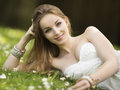 Stylish sexy young woman lying in a meadow beautiful strapless dress and jewellery with wildflowers smiling at the camera Stock Photo