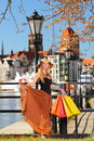 Stylish shopper woman in old town gdansk autumn hat with shopping sale bags european city the background poland europe Royalty Free Stock Images