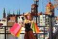 Stylish shopper woman in old town gdansk autumn hat with shopping sale bags european city the background poland europe Royalty Free Stock Photography