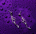 Stylish silver jewelry with water drops isolated on a violet background Royalty Free Stock Photo