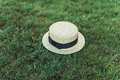 Stylish straw hat with ribbon on grass field
