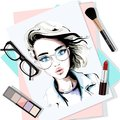 Stylish table set with hand drawn woman portrait, papers, lipstick, eyeglasses, brush and eyeshadows. Sketch.