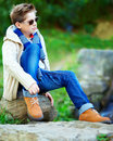 Stylish teenage boy sitting on rock outdoors fashionable Stock Photos