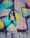 Stylish teenage girl in colorful sunglasses drinking juce near g graffiti wall Stock Photography