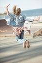 Stylish teenage girl jumping at skateboard park