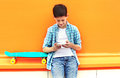 Stylish teenager boy with skateboard using smartphone in city Royalty Free Stock Photo