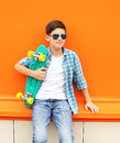 Stylish teenager boy wearing a checkered shirt, sunglasses and skateboard Royalty Free Stock Photo