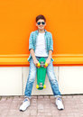 Stylish teenager boy wearing a checkered shirt, sunglasses and skateboard in city Royalty Free Stock Photo
