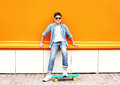 Stylish teenager boy wearing a checkered shirt, sunglasses on skateboard in city Royalty Free Stock Photo