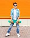 Stylish teenager boy wearing a shirt, sunglasses and skateboard Royalty Free Stock Photo