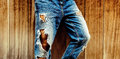 Stylish torn blue jeans on wooden background. unisex style Royalty Free Stock Photo