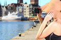 Stylish traveler woman with camera old town gdansk female photographer taking pictures autumn in hat outdoors in european city in Stock Photo