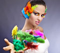 Stylish woman with colorful feathers or fashionable in her hair and in her hand Stock Photography