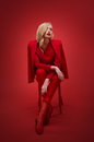 Stylish woman in red suit in studio over background Royalty Free Stock Photography
