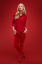 Stylish woman in red suit in studio over background Stock Image