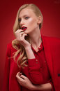 Stylish woman in red suit in studio over background Royalty Free Stock Photo