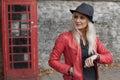 Stylish woman waiting outside a telephone kiosk Royalty Free Stock Photo