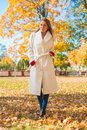 Stylish woman walking through an autumn park slender young in elegant white overcoat Stock Photo