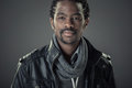 Stylish young african man in studio fashion portrait of handsome isolated on grey background with leather jacket Royalty Free Stock Photos