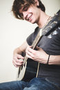 Stylish young blonde hipster man playing guitar Royalty Free Stock Photo