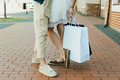 Stylish young couple holding shopping bags while standing together