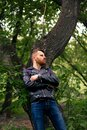 Stylish young guy in a black leather jacket and blue jeans thoughtfully looks to the right, leaning his back against a tree with h Royalty Free Stock Photo