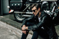 Stylish young man in leather jacket and sunglasses sitting on concrete curb near motorbike Royalty Free Stock Photo