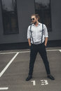 Stylish young man smoking cigarette and standing with hands in pockets Royalty Free Stock Photo