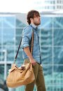 Stylish young man walking with travel bag side view portrait of a Stock Images