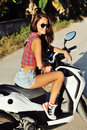 Stylish young woman on a motorcycle Royalty Free Stock Photo