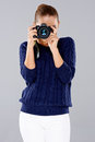 Stylish young woman photographer taking a photograph on a professional dslr camera pointing the lens directly at the viewer Royalty Free Stock Photography