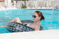 Stylish young woman relaxing in a swimming pool lying floating comfortable tube as she enjoys her summer vacation Royalty Free Stock Images