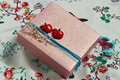 Stylishly decorated present box with a red apples and a blue ribbon Stock Photos