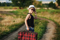 Stylishly dressed boy in field with suitcase Royalty Free Stock Photo