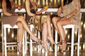 Stylishly dressed women sitting at the bar low section of three legs crossed Royalty Free Stock Photos