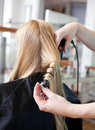 Stylist curling womans hair in beauty salon Stock Photos