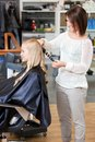 Stylist curling womans hair of a young blond customer Royalty Free Stock Images
