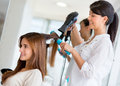 Stylist drying hair of a female client at the beauty salon Royalty Free Stock Photography