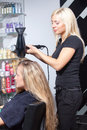 Stylist drying woman hair Stock Photography