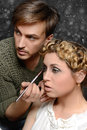 Stylist and his model applies makeup to a on abstract background Royalty Free Stock Photos