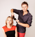 Stylist straitening  hair by flat iron Royalty Free Stock Images