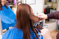 Stylist Using Flat Iron on Hair of Brunette Client Royalty Free Stock Photo