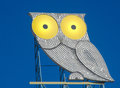 Stylized owl with yellow eyes on a roof with blue sky Royalty Free Stock Photo