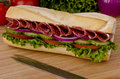 Submarine sandwich sub on a cutting board tomatoes and lettuce background Stock Photo