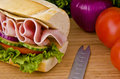 Submarine sandwich sub on a cutting board tomatoes onion and lettuce background Royalty Free Stock Images