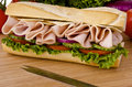 Submarine sandwich sub on a cutting board tomatoes onion and lettuce background Stock Photo