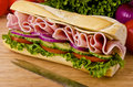 Submarine sandwich sub on a cutting board tomatoes onion and lettuce background Stock Images