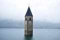 Submerged tower of reschensee church deep in Resias Lake of Bolzano or bozen, Italy Royalty Free Stock Photo